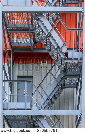 Metal Fire Escape With Handrails Of Grey Colour Located On Orange White Commercial Building With Doo