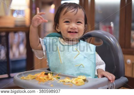Cute Happy Smiling Asian Toddler Baby Girl Eating By Hands, Little Kid Eating Food With Blw Method,