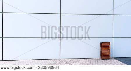 White Wall Of Commercial Building Near Paved Sidewalk With Brown Decorative Rubbish Bin Under Bright