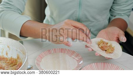 Woman making meat dumpling at home