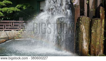 Artificial waterfall in chinese garden with rainbow