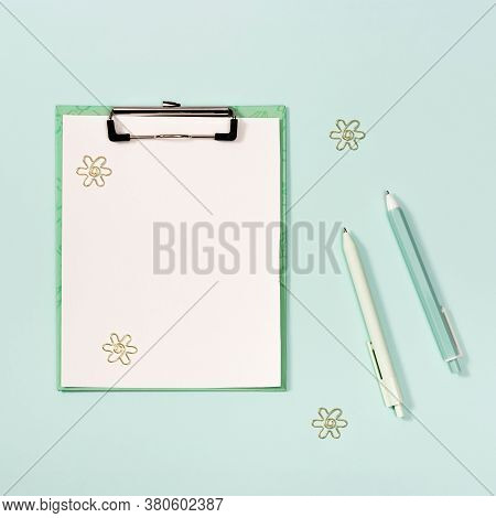 Flat Lay With Mock-up Paper Tablet With Clip, Blue And White Colored Pens, Metal Paperclips. Backgro