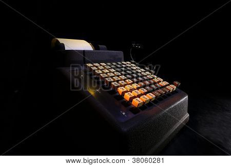 A dramatic lighting photo of an old adding machine's keyboard poster