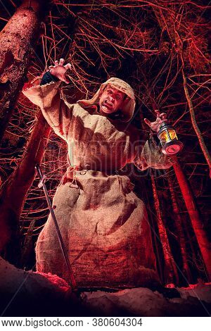 Terrible Medieval Monk In Canvas Sackcloth Robe With Lattern In Dark Forest And Red Light Of Moon On
