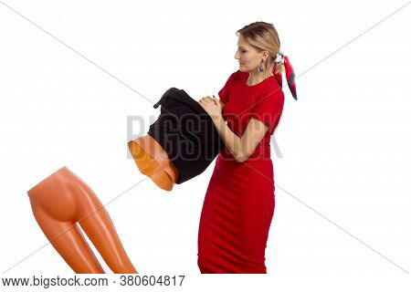 A Young Woman In A Red Dress, Puts A Black Dress On A Mannequin. The Mannequin Has Collapsed And Is