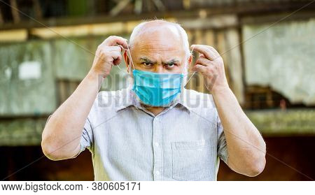 Old Man Wearing Face Mask. Portrait Of An Old Man, Years Old, In A Medical Mask. Concept Danger Of C