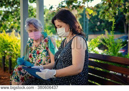 Companion Teaches A Senior Adult Woman How To Use A Computer Tablet. Both Wear Protective Masks Sitt