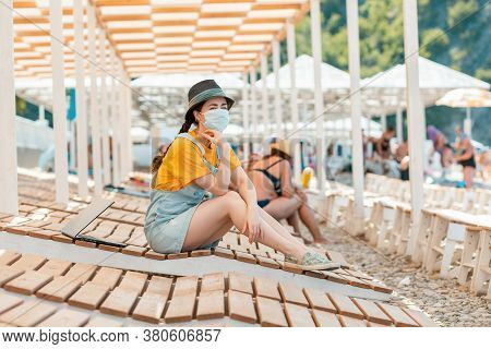 A Young Woman Is Sitting On A Chaise Longue In A Medical Mask, Next To Her Laptop. Beach Umbrellas I
