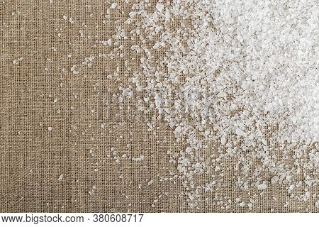 White Large Sea Salt Scattered On Sackcloth In The Right Corner. Coarse Crystals Seasalt On Natural