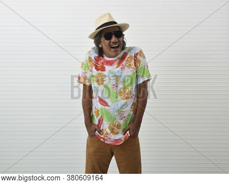Laughing Happy Elderly Traveler Asian Man Wearing Summer Shirt, Straw Hat And Sunglasses Standing Ov