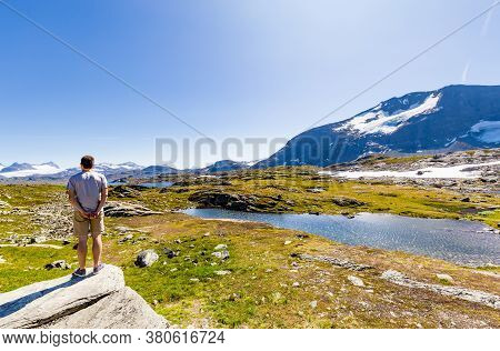 Man Enjoying The Beautiful Landscape Along National Scenic Route Sognefjellet Between Skjolden And L