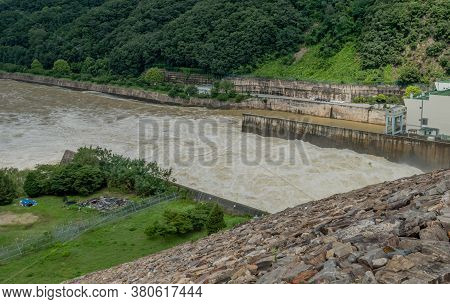Looking Down On Water Surging Through Spillway At Dam After Torrential Monsoon Rains.