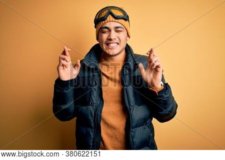 Young brazilian skier man wearing snow sportswear and ski goggles over yellow background gesturing finger crossed smiling with hope and eyes closed. Luck and superstitious concept.