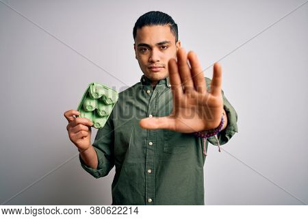 Young brazilian man holding carton box of healthy fresh eggs over white background with open hand doing stop sign with serious and confident expression, defense gesture