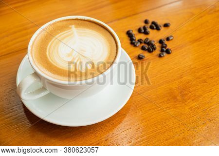 Hot Coffee Cup On An Old Brown Wooden Table With Roasted Coffee Beans Sprinkled Beside A Hot Coffee