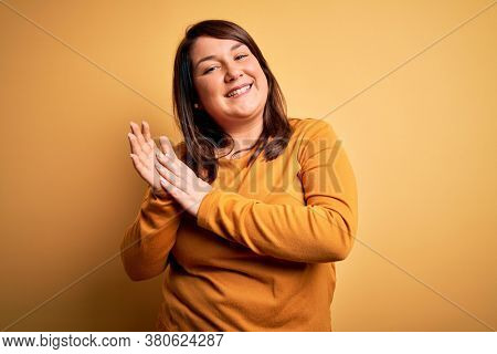 Beautiful brunette plus size woman wearing casual sweater over isolated yellow background clapping and applauding happy and joyful, smiling proud hands together