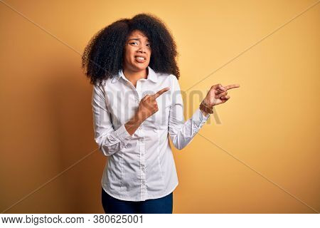 Young beautiful african american elegant woman with afro hair standing over yellow background Pointing aside worried and nervous with both hands, concerned and surprised expression