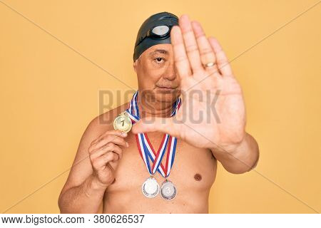 Middle age senior swimmer man wearing swimsuit, cap and goggles holding winner medals with open hand doing stop sign with serious and confident expression, defense gesture