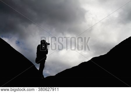 Silhouette Of A Man In The Mountains Is Taking Pictures Of The Landscape