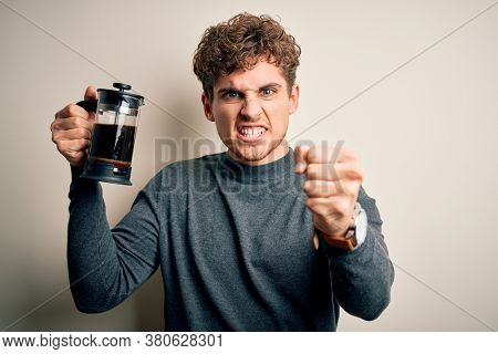 Young blond man with curly hair making coffee using coffemaker over white background annoyed and frustrated shouting with anger, crazy and yelling with raised hand, anger concept