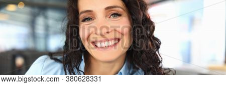 Beautiful Brunette Woman Smiles Broadly While Sitting In A Restaurant. Satisfied Employee After Lunc
