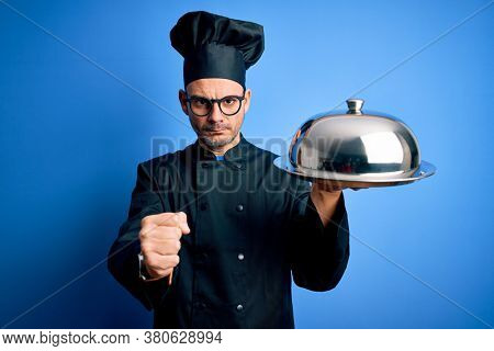 Young handsome chef man wearing uniform and hat holding waiter tray with dome annoyed and frustrated shouting with anger, crazy and yelling with raised hand, anger concept