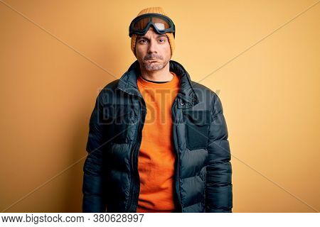 Young handsome skier man skiing wearing snow sportswear using ski goggles depressed and worry for distress, crying angry and afraid. Sad expression.