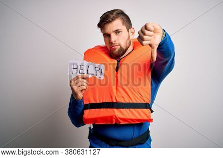 Young blond man with beard and blue eyes wearing lifejacket holding paper with help message with angry face, negative sign showing dislike with thumbs down, rejection concept