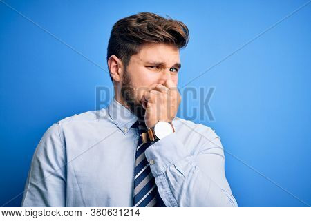 Young blond businessman with beard and blue eyes wearing elegant shirt and tie standing smelling something stinky and disgusting, intolerable smell, holding breath with fingers on nose. Bad smell