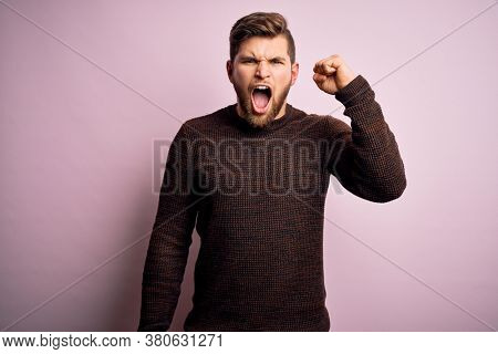 Young blond man with beard and blue eyes wearing casual sweater over pink background angry and mad raising fist frustrated and furious while shouting with anger. Rage and aggressive concept.
