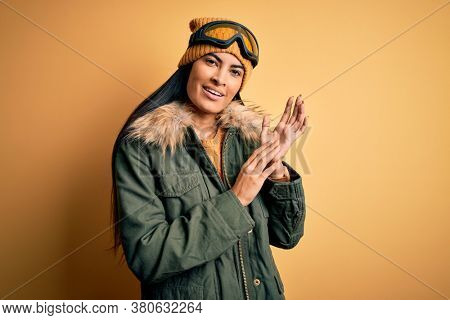 Young beautiful hispanic woman wearing ski glasses and coat for winter weather clapping and applauding happy and joyful, smiling proud hands together