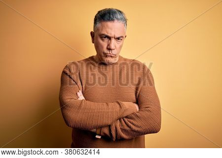 Middle age handsome grey-haired man wearing casual sweater over yellow background skeptic and nervous, disapproving expression on face with crossed arms. Negative person.
