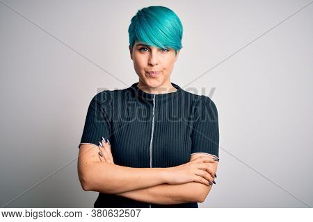 Young beautiful woman with blue fashion hair wearing casual t-shirt over white background skeptic and nervous, disapproving expression on face with crossed arms. Negative person.
