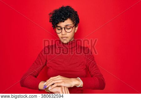 Young beautiful african american afro woman wearing turtleneck sweater and glasses Checking the time on wrist watch, relaxed and confident