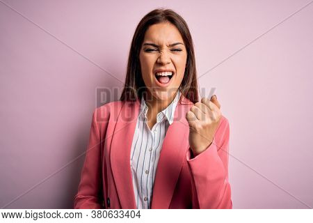 Young beautiful brunette woman wearing jacket standing over isolated pink background angry and mad raising fist frustrated and furious while shouting with anger. Rage and aggressive concept.