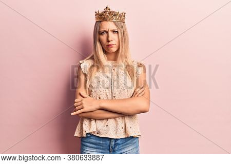 Young blonde woman wearing princess crown skeptic and nervous, disapproving expression on face with crossed arms. negative person.