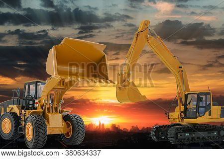 Excavators And Wheel Loader  In The Construction Site On The Sunset Background