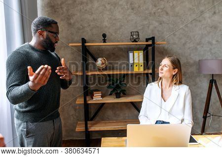 Midshot Of Two Multiracial Colleagues In Office. Young Employees In A Relaxed Atmosphere At A Mornin