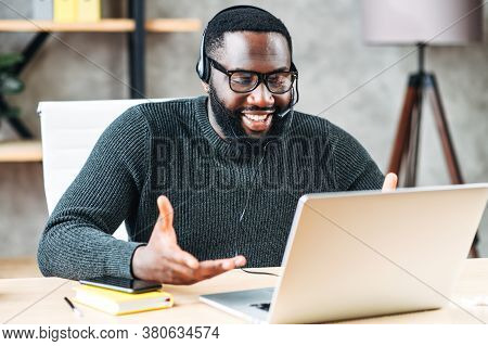 Smiling African-american Guy Uses A Handsfree Headset To Talk Online At His Workplace, Black Confide