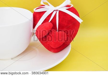 On A Yellow Background A Red Heart Stands On A White Saucer Near A Cup
