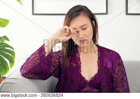 Have An Itching Eyelid, Asian Women In A Nightgown And Wear Purple Satin Robe Rubbing Her Eye Sittin