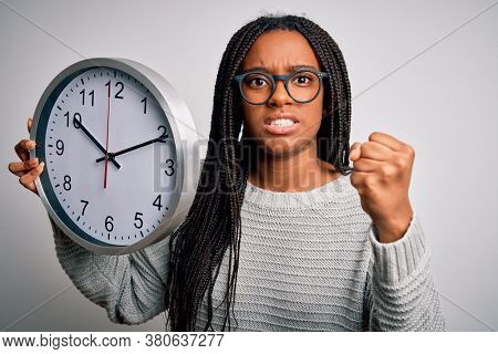 Young african american girl holding big minute clock over isolated background annoyed and frustrated shouting with anger, crazy and yelling with raised hand, anger concept