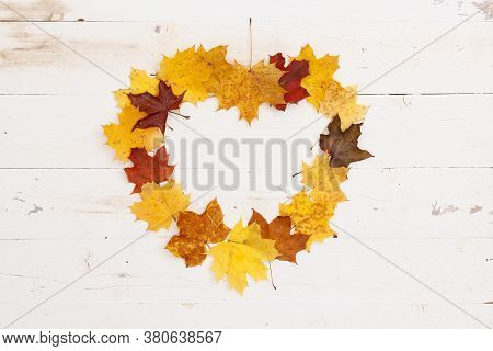 Many Colored Maple Leaves Lie On A White Textured Wooden Table. Heart Shaped Frame From Autumn Leave