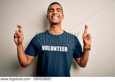 Young handsome african american man volunteering wearing t-shirt with volunteer message gesturing finger crossed smiling with hope and eyes closed. Luck and superstitious concept.