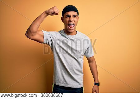 Handsome african american sportsman doing sport wearing sportswear over yellow background angry and mad raising fist frustrated and furious while shouting with anger. Rage and aggressive concept.