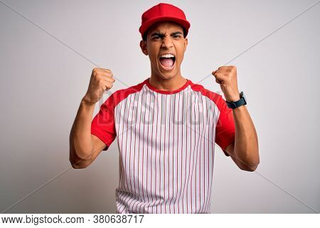 Young handsome african american sportsman wearing striped baseball t-shirt and cap angry and mad raising fists frustrated and furious while shouting with anger. Rage and aggressive concept.