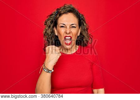 Middle age senior brunette woman wearing casual t-shirt standing over red background angry and mad raising fist frustrated and furious while shouting with anger. Rage and aggressive concept.