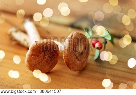 nature and environment concept - lactarius rufus mushrooms and cowberry on wooden background