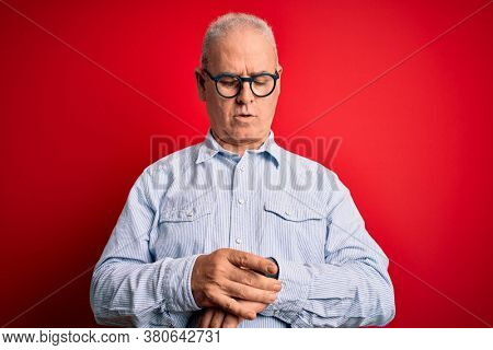 Middle age handsome hoary man wearing casual striped shirt and glasses over red background Checking the time on wrist watch, relaxed and confident