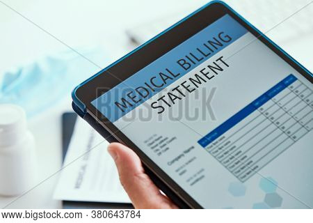closeup of a caucasian doctor man, sitting at his office desk, checking a medical billing statement in a digital tablet
